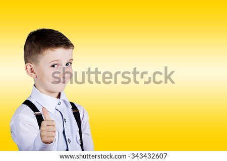 Little boy with thumb up gesture isolated over yellow background.Portrait of confident happy little boy showing thumbs up gesture wearing costume  isolated over yellow background.Funny,Happiness. - stock photo