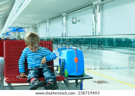little boy with touch pad waiting in the airport, travel concept - stock photo