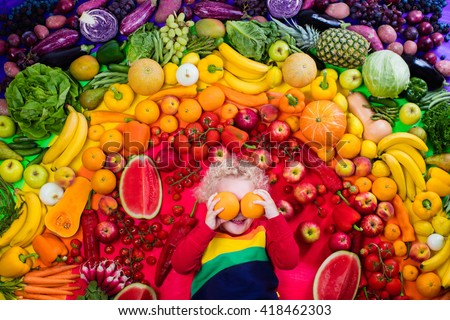 Little boy with variety of fruit and vegetable. Colorful rainbow of raw fresh fruits and vegetables. Child eating healthy snack. Vegetarian nutrition for kids. Vitamins for children. View from above. - stock photo