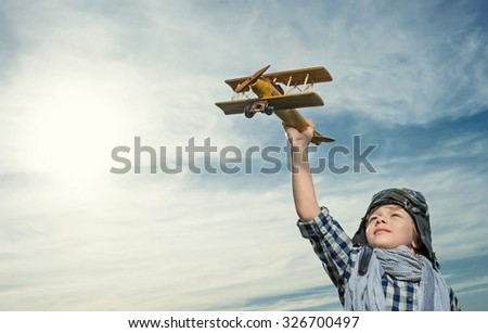 Little boy with wooden airplane outdoors - stock photo