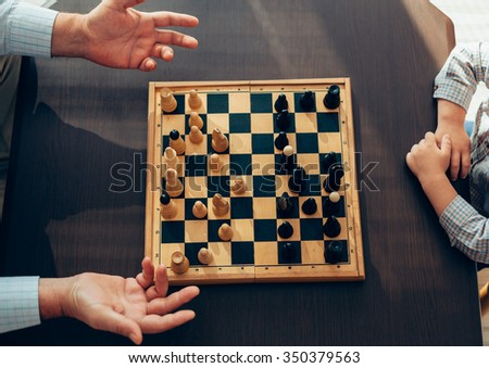 Little boy won his grandfather in chess - stock photo
