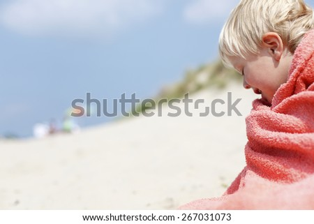 Little boy wrapped in towel at beach - stock photo