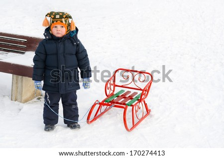 Little boy wrapped up warmly against the cold winter weather standing in the snow with his toboggan - stock photo