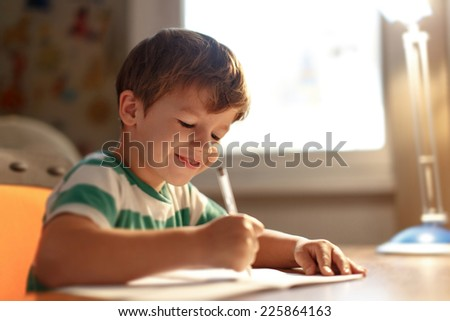 Little boy write into exercise book, smile, education - stock photo