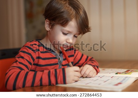 Little boy write math homework at home, primary school - stock photo