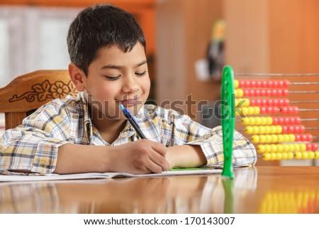 Little boy writing homework - stock photo