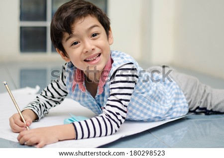 Little boy writing white paper on the floor - stock photo