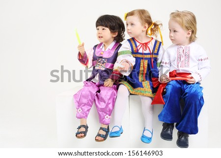 Little boys and girl in folk costumes sits with sticks on white background. - stock photo
