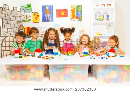 Little boys and girls constructing toy houses - stock photo
