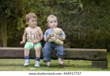 Little boys having fun together outdoors in the garden - stock photo