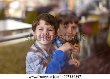 Little boys in fast food restaurant behind glass eating french fries - stock photo