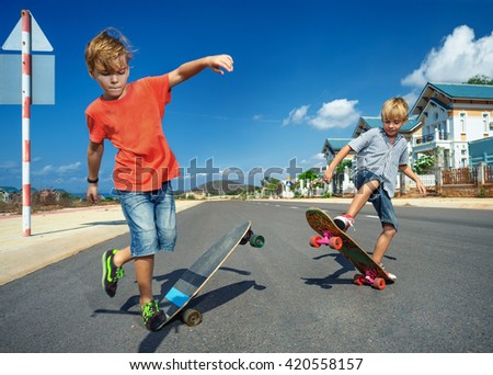 Little boys on longboard skate  - stock photo