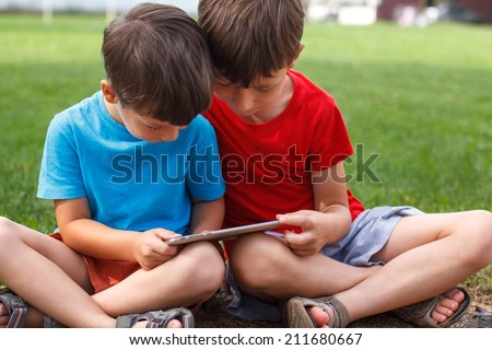 Little boys sit and play with tablet at outdoor, wireless technology, computer generation - stock photo