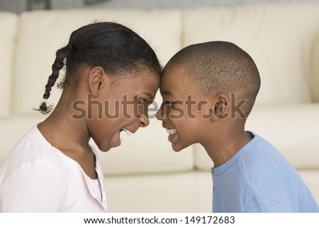 Little brother and sister butting heads - stock photo