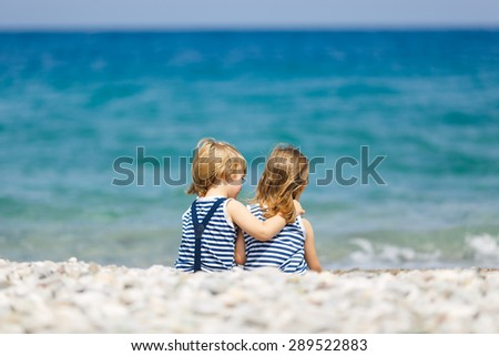 Little brother and sister walking on the beach - stock photo
