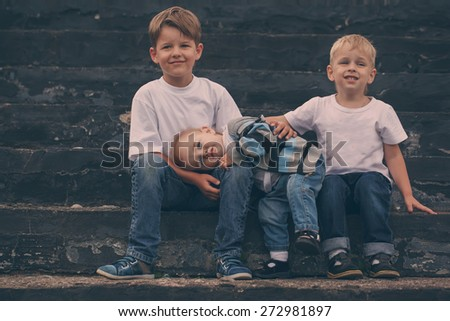Little brother embracing with the brothers while sitting on a bench - stock photo