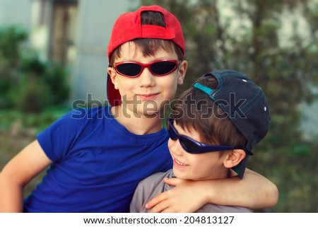 Little brothers in cap and sunglasses play outdoor - stock photo