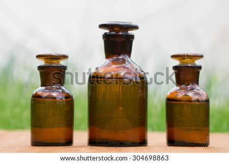 little brown bottles on booden board and green grass - stock photo