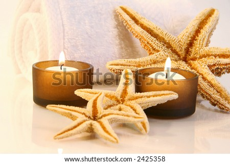Little brown candles, towel and starfish with a warm glow - stock photo