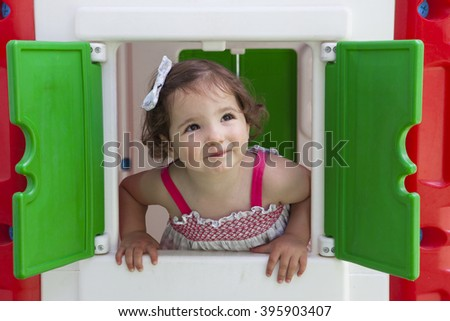 Little brown hair girl smiling through the window of kids playhouse - stock photo