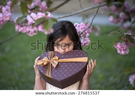 Little brunette girl looking forward with big brown heart shaped gift box standing among japanese cherry blossom in the park, horizontal picture  - stock photo