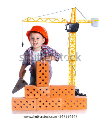 Little builder. Boy in a helmet plays in the builder with bricks. Isolated on a white background. - stock photo