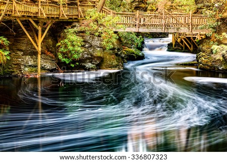 Little Bushkill creek meanders through the forest and leaves long exposure foam trails under wooden bridges. Bushkill Creek is a tributary of the Delaware River in eastern Pennsylvania - stock photo