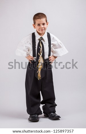 Little business boy in over sized large suit - stock photo