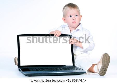 Little business boy in  solid white suit sitting at notebook on a white background - stock photo
