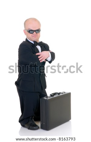 Little businessman, dwarf in a formal suit with bow tie next to  suitcase, studio shot, white background - stock photo