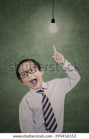 Little businessman is shouting under lit bulb in class - stock photo
