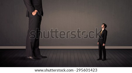 Little bussinesman in front of a giant boss legs concept on background - stock photo