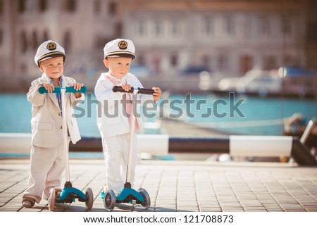 Little captains against the sea and pier - stock photo