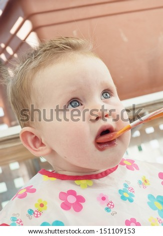 Little caucasian baby feeding with a spoon. - stock photo
