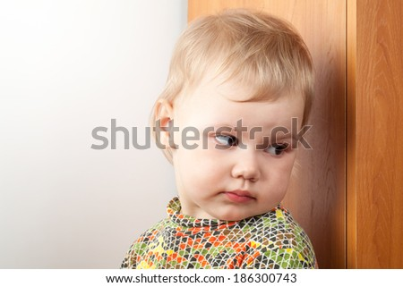Little Caucasian baby girl hiding behind a cupboard - stock photo