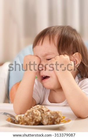 Little Caucasian baby with food and crying at the table - stock photo