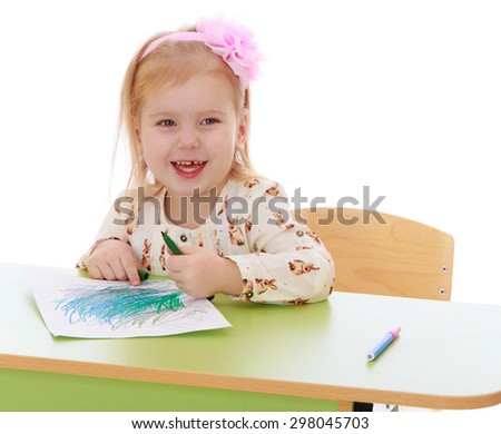 Little Caucasian blond girl draws with pencils sitting at the table , the girl laughs-Isolated on white - stock photo