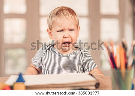Little caucasian boy crying and crayons is in front - stock photo