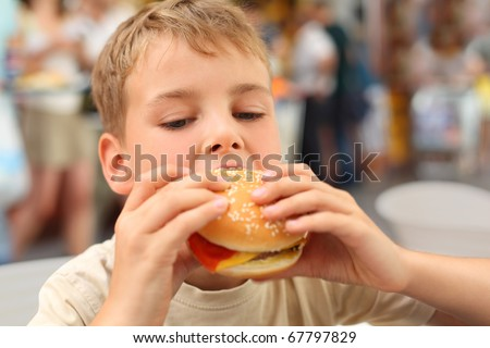 little caucasian boy eating burger, looking down - stock photo