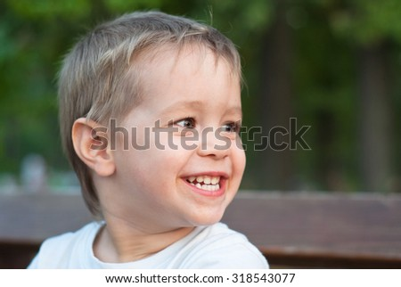Little caucasian boy looks away and smiling outdoors - stock photo