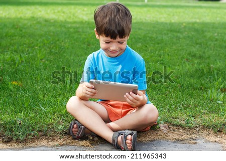 Little caucasian boy smile with tablet outdoor - stock photo