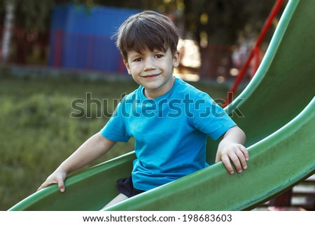 Little caucasian boy smiling on slide, outdoor - stock photo