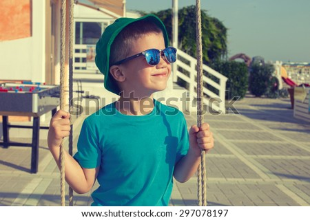 Little caucasian boy swinging outdoor on sunny summer day, vintage style - stock photo