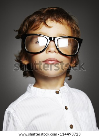 little caucasian boy with black glasses on grey background - stock photo