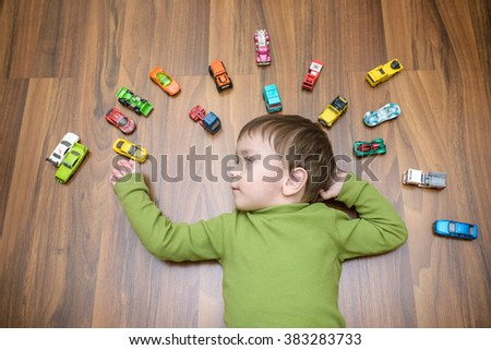 Little caucasian child playing with lots of toy cars indoor. Kid boy wearing green shirt. Happy preschool child having fun at home or nursery. - stock photo