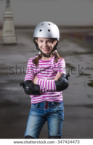 Little caucasian cute girl wearing a roller protection and helmet - stock photo