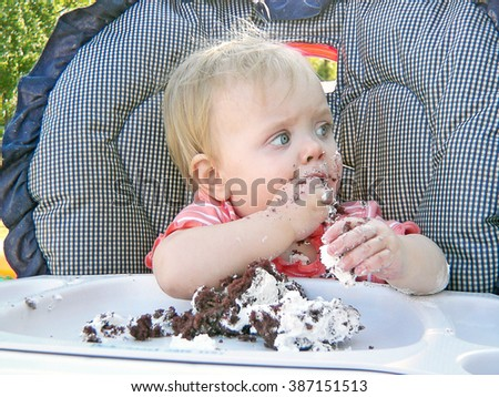 little Caucasian girl in a high chair eating chocolate birthday cake with her fingers - stock photo