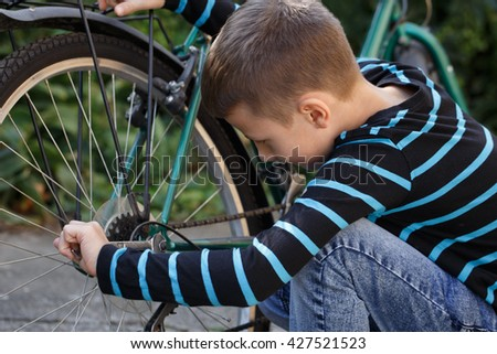Little caucasian schoolboy repair bicycle at outdoor - stock photo