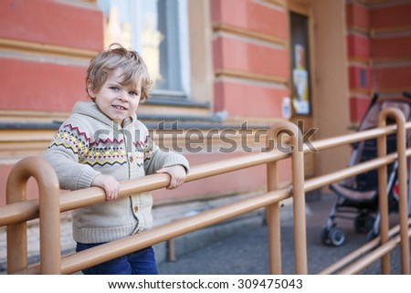 Little caucasian toddler boy of two years having fun in spring city, outdoors - stock photo