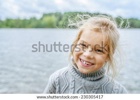 Little cheerful beautiful girl in sweater on background of autumn lake. - stock photo